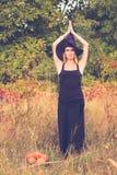 巫婆服装实践的瑜伽的白肤金发的妇女 图库摄影