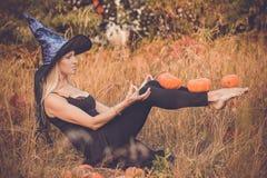 巫婆服装实践的瑜伽的笑的女孩 免版税图库摄影