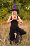 巫婆服装实践的瑜伽的笑的女性 库存照片