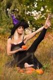 巫婆服装实践的瑜伽的美丽的女孩 免版税图库摄影