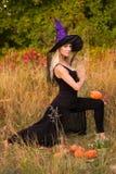 巫婆服装实践的瑜伽的美丽的妇女 免版税库存图片