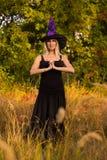 巫婆服装实践的瑜伽的高兴的女性 免版税库存照片