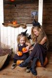 巫婆服装的两个妹坐南瓜 万圣夜的概念 免版税库存照片
