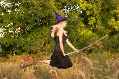 巫婆服装的俏丽的女孩在帚柄飞行 库存照片
