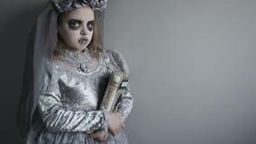 巫婆服装的女孩握书咒语腋窝 万圣夜,巫术,死者的天 影视素材