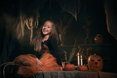 巫婆服装的小女孩坐桌 免版税库存图片