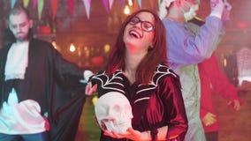 巫婆服装的年轻美丽的十几岁的女孩在她的手上握一块头骨 股票视频
