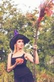 巫婆服装的美丽的女孩有帚柄的 免版税图库摄影
