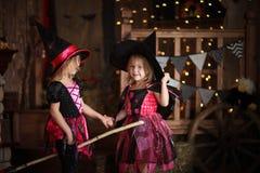 巫婆服装的滑稽的儿童女孩万圣夜黑暗backg的 库存照片