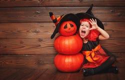 巫婆服装的滑稽的儿童女孩为万圣夜用南瓜Ja 免版税库存照片