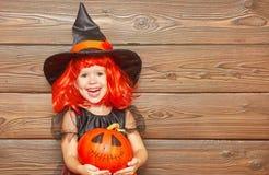 巫婆服装的滑稽的儿童女孩为万圣夜用南瓜Ja 免版税库存图片