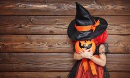 巫婆服装的滑稽的儿童女孩为万圣夜用南瓜Ja 免版税图库摄影