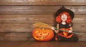 巫婆服装的滑稽的儿童女孩为万圣夜用南瓜Ja 图库摄影