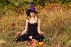 巫婆服装训练莲花姿势的女孩 库存照片