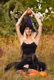 巫婆服装训练莲花姿势的白肤金发的女孩 免版税库存图片