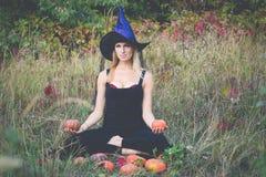巫婆服装训练莲花姿势的高兴的女孩 库存图片