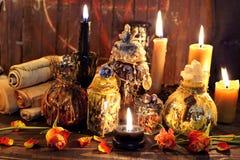 巫婆瓶、黑蜡烛和玫瑰agains板条与五角星形 库存照片