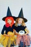 巫婆的两个小女孩打扮使用用南瓜 免版税库存照片