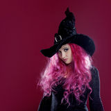 巫婆的帽子和服装可爱的妇女有红色头发的执行在桃红色背景的魔术 万圣夜,恐怖题材 免版税库存图片