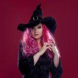 巫婆的帽子和服装可爱的妇女有红色头发的执行在桃红色背景的魔术 万圣夜,恐怖题材 免版税库存照片