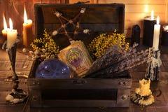 巫婆箱子用愈合的草本、水晶球、占卜用的纸牌和灼烧的蜡烛 免版税图库摄影