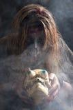巫婆观看一块头骨 库存照片