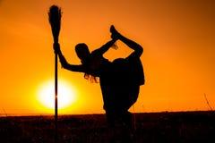年轻巫婆跳舞剪影在帚柄的 库存图片