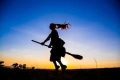 年轻巫婆飞行剪影在帚柄的在天空 库存图片