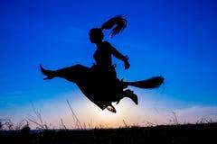 年轻巫婆飞行剪影在帚柄的在天空 免版税库存图片