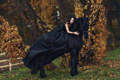 巫婆黑寡妇女王/王后在恐怖黑暗森林里拥抱她的黑马 免版税图库摄影