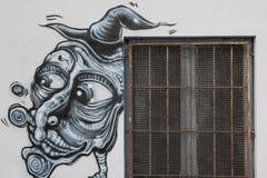 巫婆,在公开墙壁上的Befana Grafito在与生锈的格栅,街道艺术街道画,万圣夜题材的窗口附近 免版税库存照片