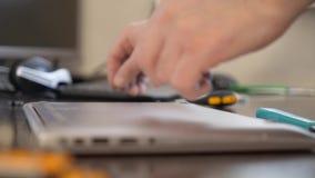 巫术师使用一把螺丝刀扭转在笔记本的盒盖的螺丝 股票录像
