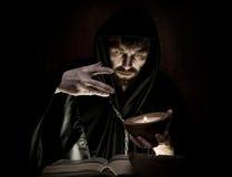 巫术师由在黑暗的背景的烛光降从厚实的古老书的咒语 免版税库存照片