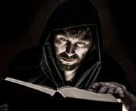 巫术师由在黑暗的背景的烛光降从厚实的古老书的咒语 图库摄影