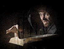 巫术师由在黑暗的背景的水下落降从厚实的古老书的咒语,在透明玻璃复盖后 图库摄影