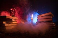 巫术师的书桌 蜡烛光点燃的书桌 一块人的头骨,在沙子的旧书浮出水面 万圣夜与diffe的静物画背景 免版税库存图片