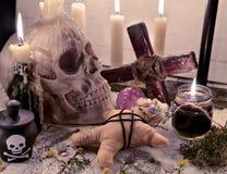 巫毒教与头骨、玩偶和灼烧的蜡烛的静物画 免版税图库摄影