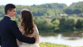 已婚夫妇、新娘佩带的婚礼礼服和新郎有黑衣服的,反映美丽的山森林的湖 股票视频