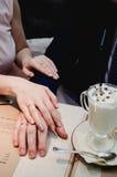 已婚夫妇举行手和出现婚戒在咖啡馆 库存图片