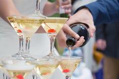 已婚夫妇倾吐的闪耀的起泡的香槟到玻璃里 免版税库存图片