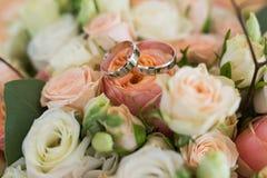 已婚夫妇的手与金黄圆环的 说谎在与橙色和米黄玫瑰的婚礼花束的两个婚姻的金黄圆环 库存图片
