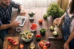 已婚夫妇谈话,当在家时烹调在厨房里 免版税库存图片
