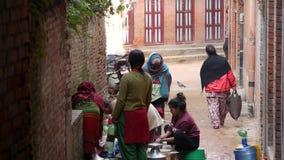 巴克塔普尔,尼泊尔- 10月13日2018在寺庙墙壁附近的人洗涤物 洗涤头发和衣裳用水的观点的妇女 股票录像