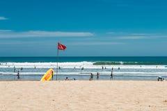 巴厘岛海滩印度尼西亚kuta 海浪拯救点 黄色抢救冲浪板和红旗 免版税库存图片