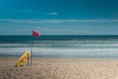 巴厘岛海滩印度尼西亚kuta 海浪拯救点 黄色抢救冲浪板和红旗 免版税库存照片