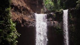 巴厘岛瀑布,下来水goind与在慢动作,在狂放的绿色密林附近的瀑布的巨大的力量在雨以后 股票录像