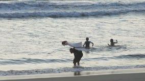 巴厘岛,印度尼西亚, 2017年10月:孩子获得乐趣在海浪库塔海滩巴厘岛 股票录像