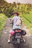 巴厘岛,印度尼西亚- 2017年11月25日:一辆摩托车的年轻愉快的妇女在热带巴厘岛的密林雨林 图库摄影