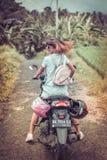 巴厘岛,印度尼西亚- 2017年11月25日:一辆摩托车的年轻愉快的妇女在热带巴厘岛的密林雨林 库存图片