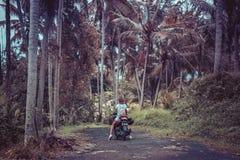 巴厘岛,印度尼西亚- 2017年11月25日:一辆摩托车的年轻愉快的妇女在热带巴厘岛的密林雨林 免版税图库摄影